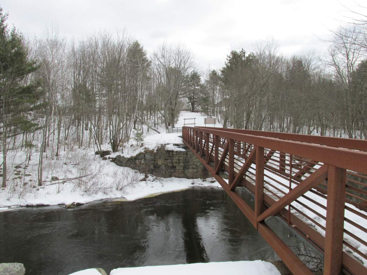 Dover NH snow removal services are offered. This is an image of a snowy bridge in the town that travels over the river.